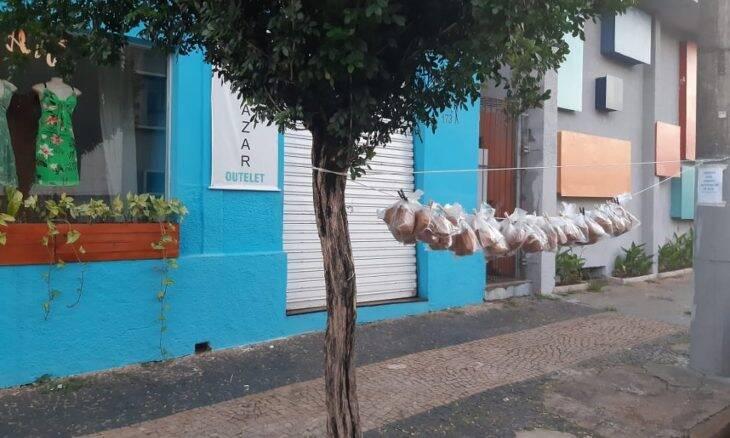 Voluntários penduram lanches em varal para ajudar moradores de rua
