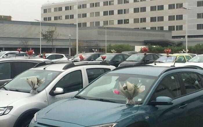 Florista distribui buquês de flores em estacionamento de hospital